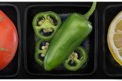 a triptych depicting high resolution close ups of a pristine tomato, a  green jalepeno and a slice of lemon