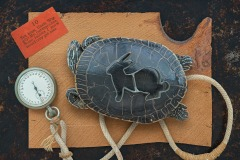 """a closeup vignette of a tortoise with a rabbit stencil on its back atop a rough edged plank with stopwatch in frame. A card states """"Ten hops, Uncle Wiggily! My, but that's fine, Some rabbits I know would only get nine"""""""