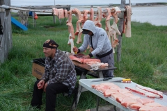 Men processing a whale with polar bear scratch marks