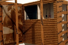 Small cardboard structure mounted on wall.