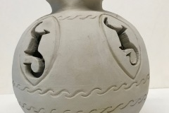 Vase form with impressed pattern, and cutouts on surface and a wide fluted ending.