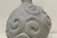 Round bellied vase form ending in a wide lip and embossed spirals on surface.