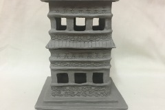 Tall pagoda shaped form with cutouts serving as implied windows.