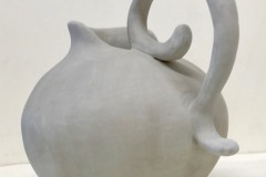 Large pitcher form with high curled handle.