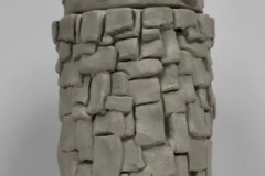 Tall jar form, rounded shape with tile like applique on surface.