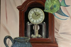 Another fantastical still life where an exotic fish swims in the air around an old timey clock. a handmade mug the same color as the fish sits before the clock.