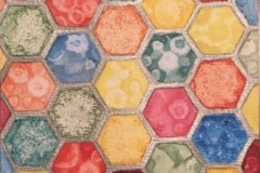 A honeycomb pattern fills the composition. within each hexagon is a different color applied in different techniques, creating a variety of textures.