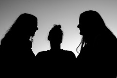 An image of three people seemingly talking in a circle, only their shapes are discernable, as their figures are black silhouettes.