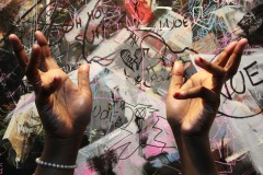 A color image of hands, with red painted nails, fingers splayed upwards towards the light source which illuminates them. The background a busy graffiti-like scrawl of colors and line.