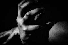 A shadowy image of the human body, only identified by two hands contorted. the rest of the image is flesh and dark negative space.