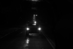 A black and white image of a line of cars at night, headlights coming towards the viewer as if the camera person is standing in the line of traffic ( or maybe in the back of a car).