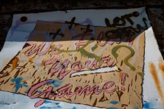"""An image of a deteriorating sign once stating """" We Play Your Game"""". The sign is peeling away and has been spray painted over with different colored tags."""