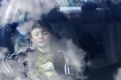 A photo of a boy taken through the windshield of a car. He sits eyes closed in the passenger seat, clouds reflecting in the glass before him.