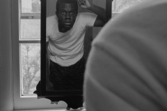 A black and white photo of a young man looking in a mirror brushing his hair. the mirror is placed in front of a window.