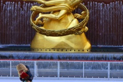 A colorful image of a child ice skating with a parent, behind them towersa large golden statue of a man.