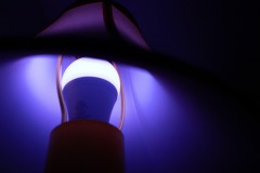 A Closeup image of the glow of a lightbulb beneat a lampshade, the color is a ultra violet hue.