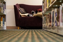 A photo taken from the floor of a library, out of focus bookshelfs direct the viewer back towards a students feet, laying on a couch amongst their books.