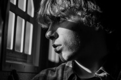 The shadowy silhouette of a young man looking through a window, the shadows of the pane across his face as he looks outward.