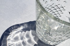 A closeup looking down at a faceted crystal cup, with the light passing through creating the strange pattern of a shadow beside it.