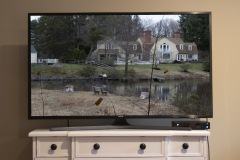 An image of a television atop a table. on the screen is a large house overlooking a pond.