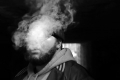 An image of a person, smoking where the smoke is billowing up the composition obscuring their eyes and nose. the background is dark but for a single illuminated door way shape.