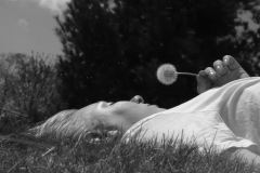 A black and white image taken laying in the grass, looking over at a friend's profile. the woman is sunlit, blowing dandelion seeds.