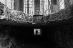 A strange perspective from a basement of an abandoned building, looking up through the broken concrete floor at the next level. A person stands in the basement in the distance.