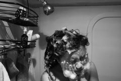 A black and white photo of a woman lathering her hair and face with soap in a shower. Her eyes are closed as suds enshroud her head.