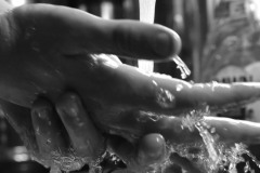 Close up of hands washing in the sink with running water.