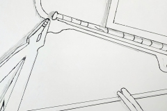 A hanger, pliers, scissors and notebook arranged at angles to eachother and cropped by the page edge.