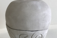 jar form, set on feet, with spiral carving at base and spiral handle.