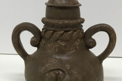 urn form with carved fish and leaves on the surface, 2 curled handles and tear drop shaped knob, glazed dark brown.