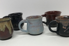 5 handled mugs, glazed brown, blue, black and red.