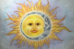 colorful rendering of a shining sun, with a womans face.the sun is embraced by a crescent moon, also with a face.