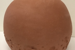 Terra cotta colored spherical jar, with crater texture at the bottom.