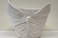 flower pot form with butterfly form sculpted on surface.