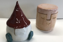 two small jars, one in the shape of a knome the other with a face carved into the surface.