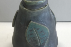 small jar with leaf pattern on surface.