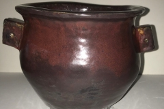 vase form with small side handles glazed red.