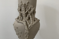 Vase form with a cherry tree in blossom sculpted onto the surface.