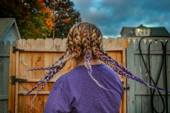 image of the back of a womans head, detailing the frozen motion of her braids flying through the air. The purple color of her hair matches her shirt.