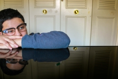 image of a man leaning his head on a highly reflective table surface.