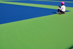 image of a woman sitting on a skateboard, with birght pink helmet, blue and green surface of the ground.