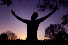 image of a mans silhouette with arms raised up.
