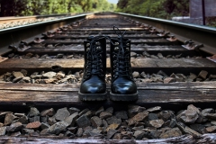 image of doc martens boots standing without a human body on the plank of a rail road track.