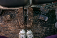 image of feet in converse all stars and a muddy floor mat in a vehicle of some sort.