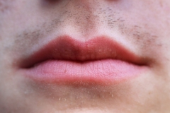 image of a young mans lips, stubble growing in.