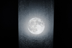image of full moon through cracked looking window.