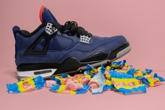 blue sneaker standing atop pile of bubble gum and wrappers.
