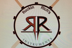 """A drum with drumsticks and side by side """"Rs"""" for Rockin Richards."""